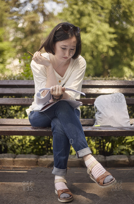 Full length of young woman reading paper while sitting on bench at park