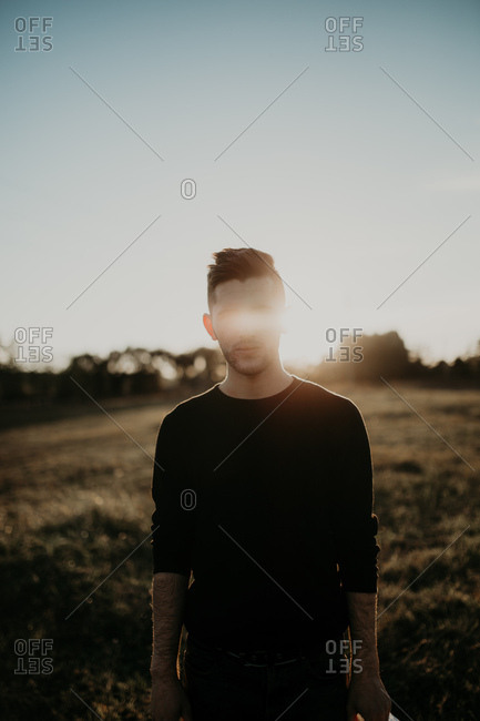Artistic portrait of a young man with sun rays in his eyes