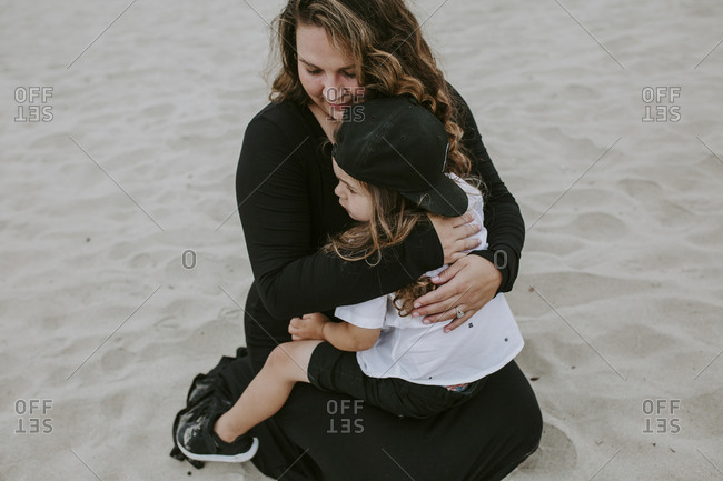 High angle view of pregnant mother embracing daughter while sitting on sand at beach