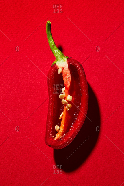 Sliced red pepper on red background