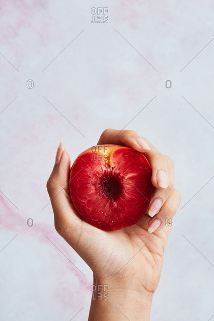 Woman's hand holding a peach with red flesh