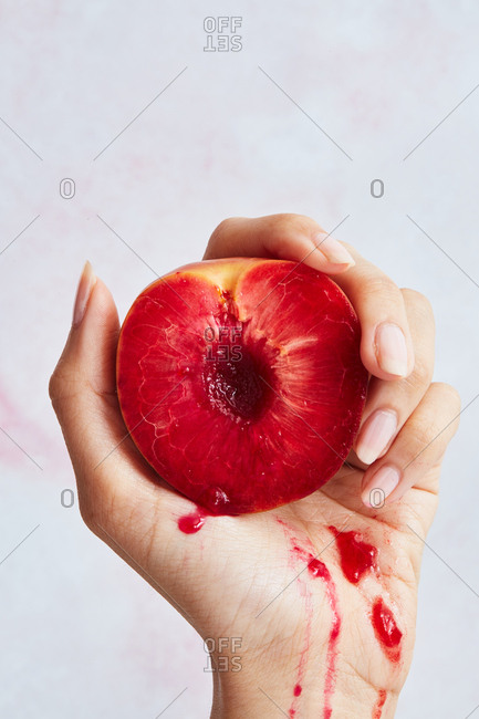 Woman's hand squeezing a peach with red flesh