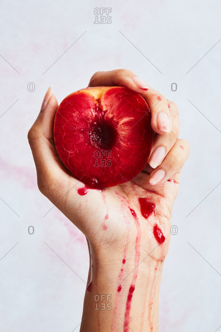 Hand squeezing a peach with red flesh