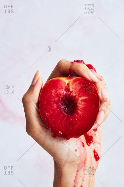 A hand squeezing a peach with red flesh