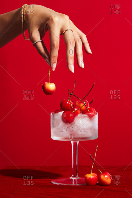 Woman placing cherries onto a glass of ice