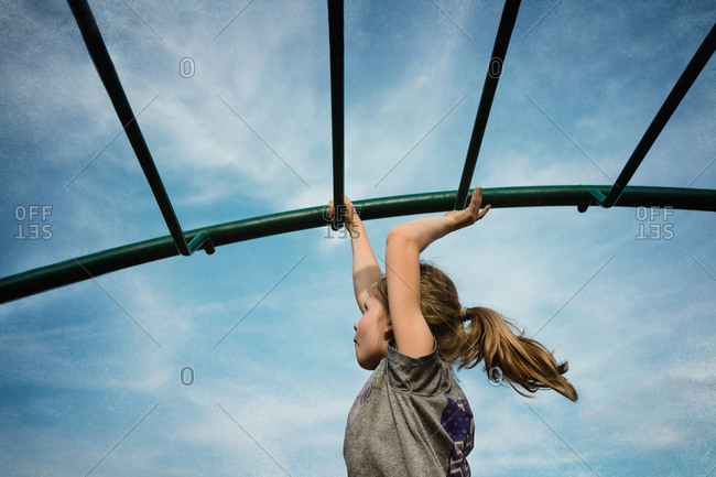 Girl swinging from monkey bars on playground
