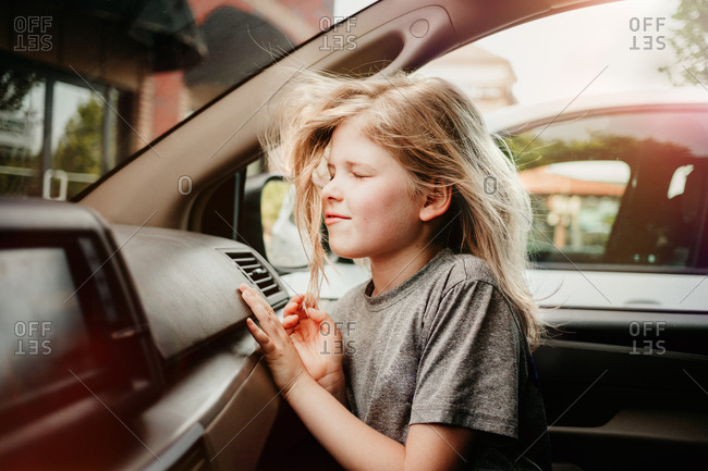 Girl cooling off inside a car with air conditioning