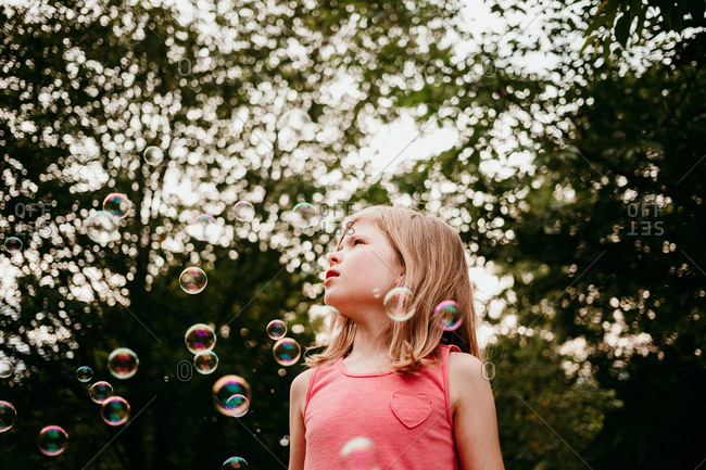 Girl surrounded by bubbles outdoors