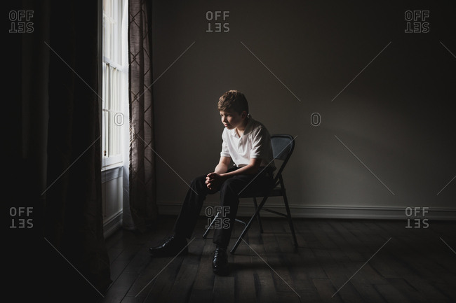 Portrait of a well dressed tween sitting in folding chair by window
