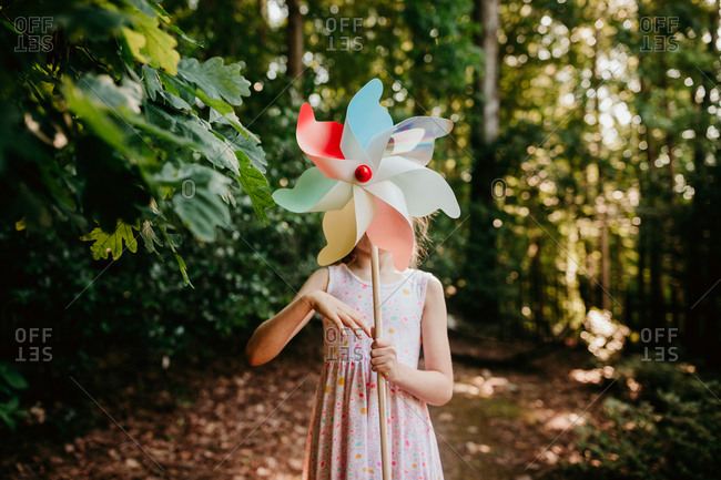 Girl in the forest spinning a pinwheel in front of her face