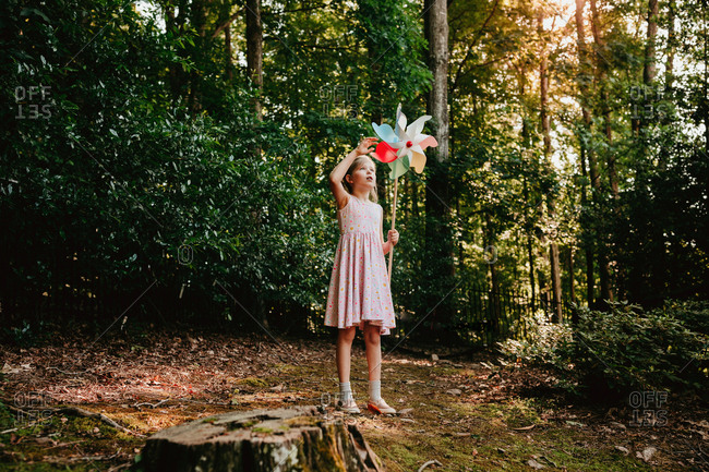 Girl in the forest spinning a pinwheel
