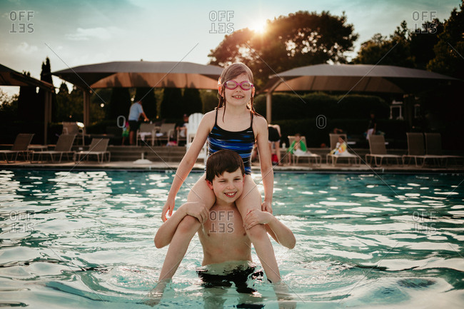 Girl sitting on boy's shoulders in pool