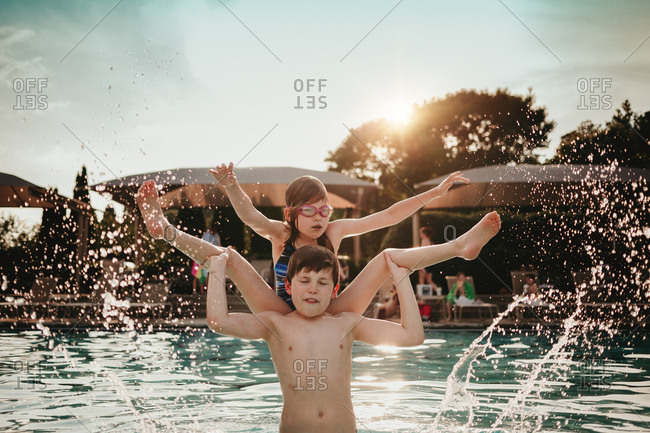 Brother flipping sister into a pool