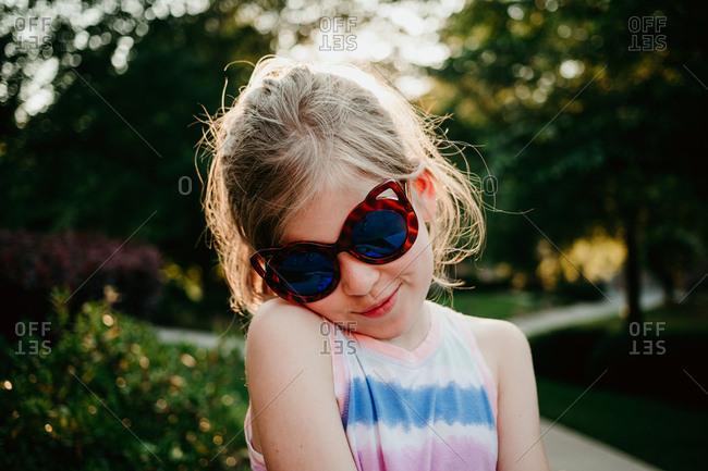 Portrait of a little blonde girl wearing cat sunglasses