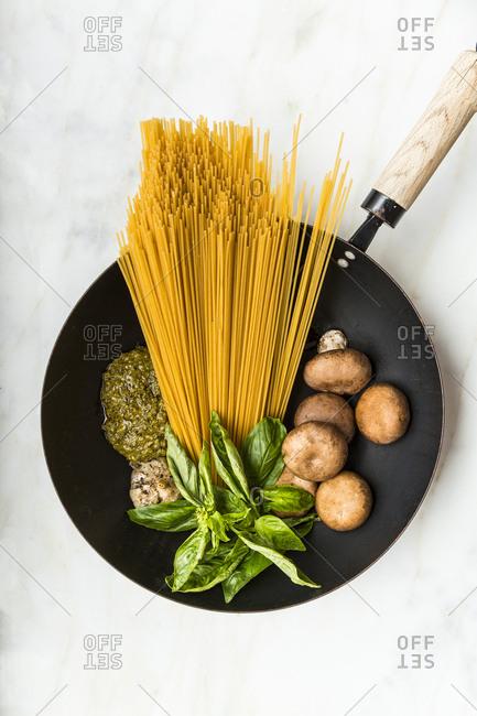 Spaghetti, mushrooms, fresh basil and pesto sauce in a wok pan