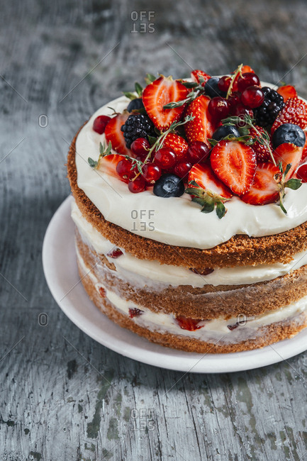 Forest fruit nude cake on a wooden surface