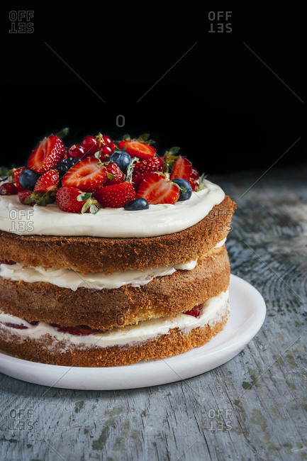 Forest fruit nude cake on a wooden surface in front of dark background