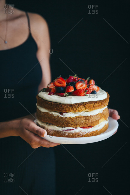 Girl holding forest fruit cake with dark background
