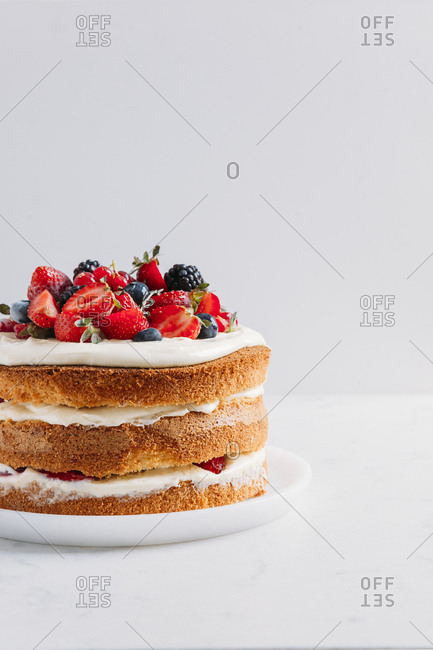Forest fruit nude cake on a white marble surface