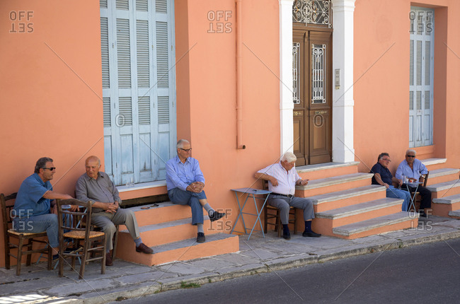 Naxos Island, Cyclades, Greece - May 29, 2019: Old men hanging out on street side in morning gossiping and having first coffee