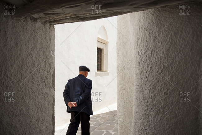 Rear view of old man walking in shopping area, Naxos Island, Cyclades, Greece