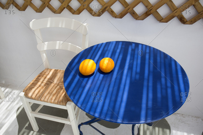 Two oranges sitting on a blue table top, IOS Island, Cyclades, Greece
