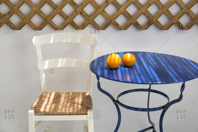 Two oranges sitting on blue table top, IOS Island, Cyclades, Greece