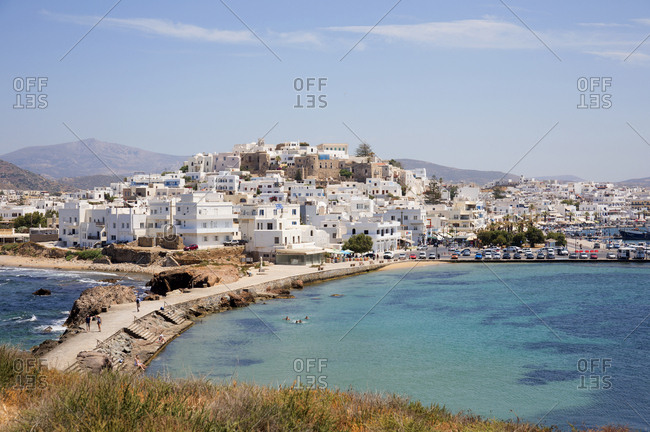 Cyclades Islands, Greece - May 29, 2019: Coastal city with dam and traditional buildings