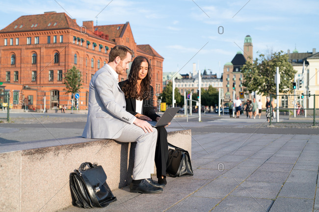 Two young businesspeople sitting outside in town working on laptop