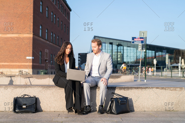Two businesspeople sitting outside in town working on laptop