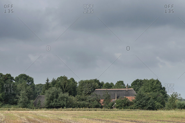 Dark clouds over country home