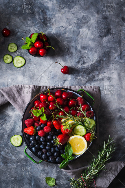Various summer fruit berries with fresh herbs, lemon and cucumber in rustic bowl on grey surface