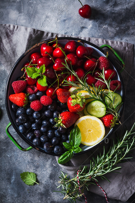 Variety of summer fruit and berries with fresh herbs, lemon and cucumber in rustic bowl on grey surface