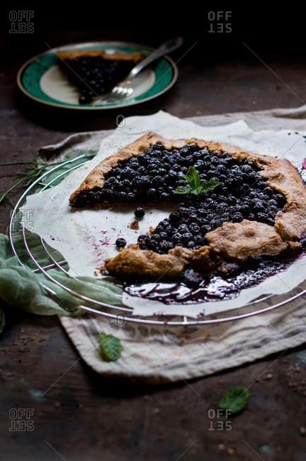 Messy aronia berry wholewheat galette decorated with fresh mint