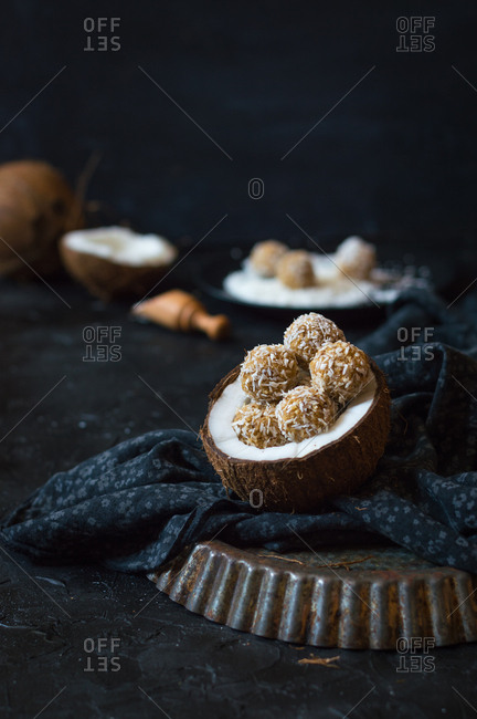 Raw coconut energy balls inside of a halved coconut