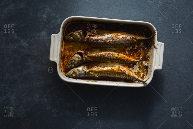 Freshly cooked mackerel in a baking dish on a dark background