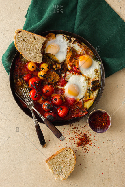 Overhead view of skillet with shakshuka and bread