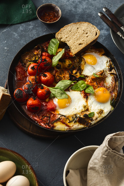 Fried eggs with vegetables in a pan close up