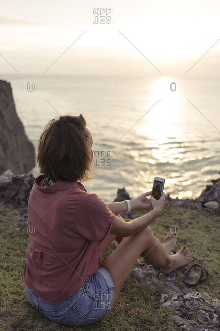 Rear view of woman taking selfie with mobile phone while sitting at beach during sunset