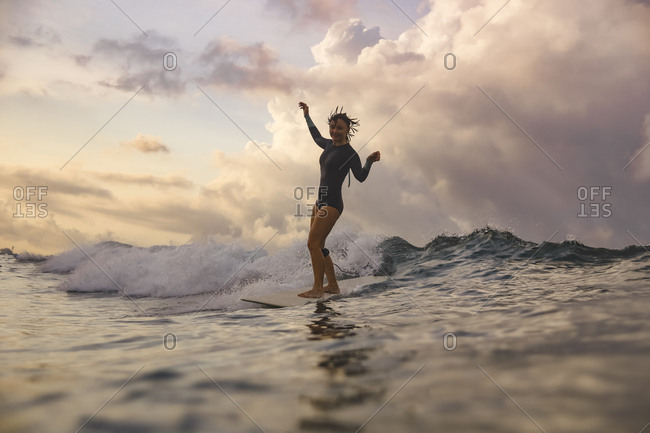 Young woman surfing at sunset