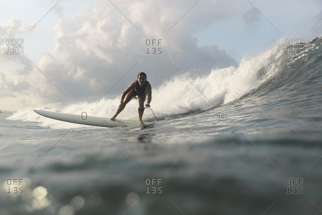 Low angle view of woman surfing in sea against sky