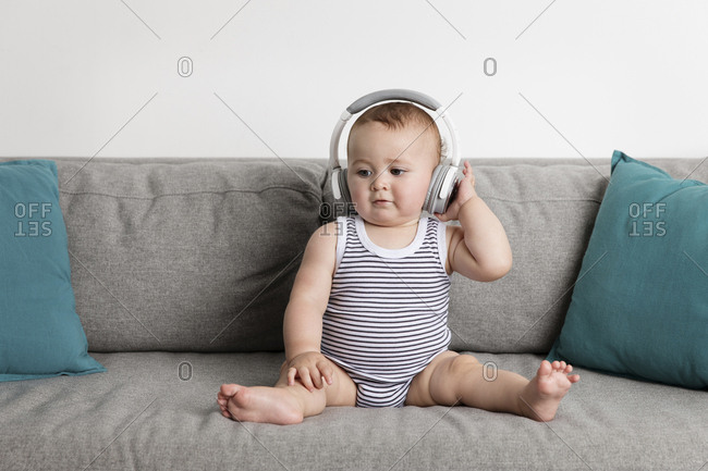 Cute baby boy listening music through headphones while sitting on sofa against wall at home