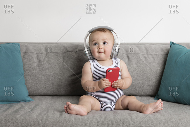 Cute baby boy holding mobile phone while listening music on sofa against wall at home