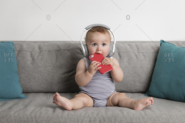Cute baby boy holding smart phone while listening music on sofa against wall at home