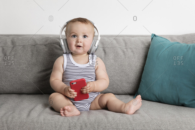 Baby boy holding mobile phone while listening music on sofa against wall at home