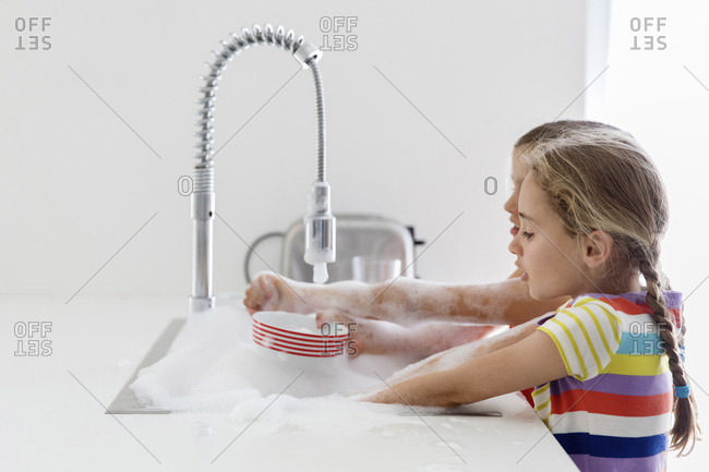 Sisters washing dishes in kitchen sink at home