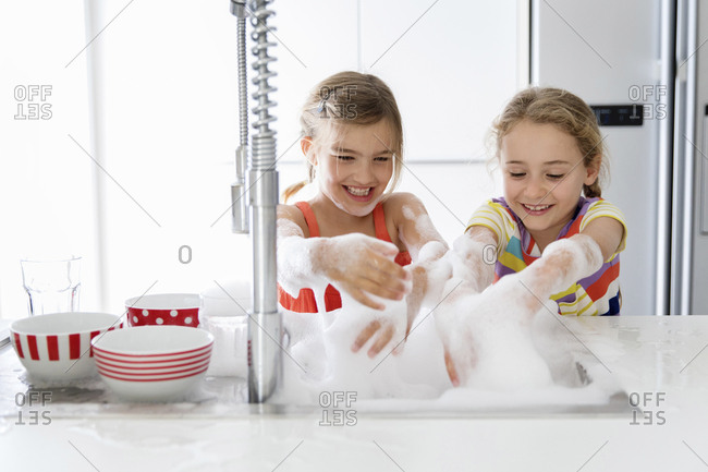 Happy sisters playing with soap sud while washing dishes in kitchen sink at home