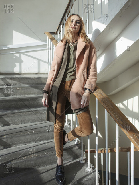 Low angle portrait of woman wearing coat while standing on steps in building