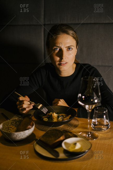 Portrait of young woman having meal at dining table in restaurant