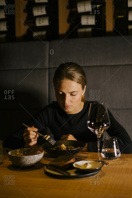 Young woman eating meal at dining table in restaurant